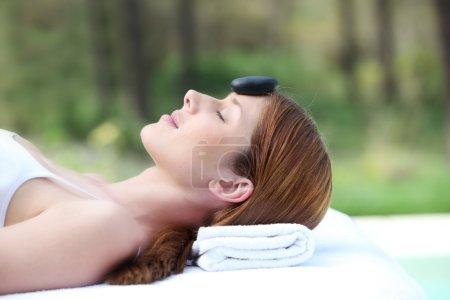 Photo pour Femme posée sur un lit de massage avec pierre chaude sur le front - image libre de droit