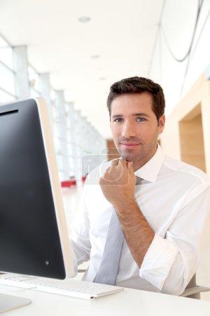 Photo pour Vendeur devant l'ordinateur de bureau - image libre de droit