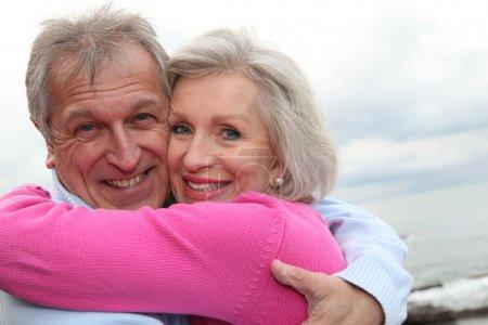Photo pour Heureux couple senior embrassant mutuellement en bord de mer - image libre de droit