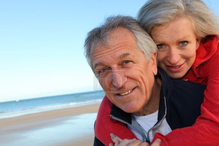 Photo for Senior man giving piggyback ride to woman by the sea - Royalty Free Image