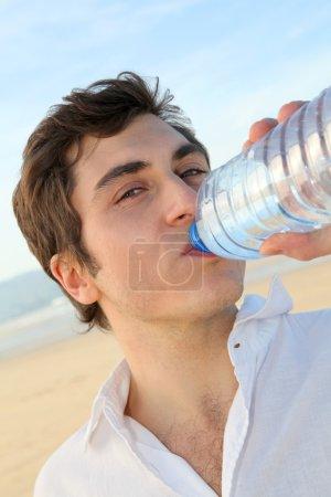 Photo pour Gros plan de l'homme buvant de l'eau de bouteille - image libre de droit