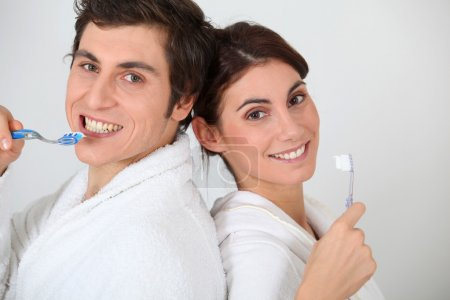 Portrait of couple brushing their teeth