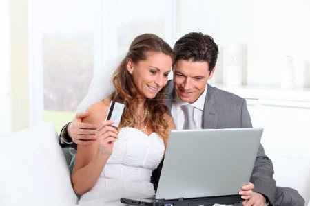 Bride and groom doing shopping on inernet