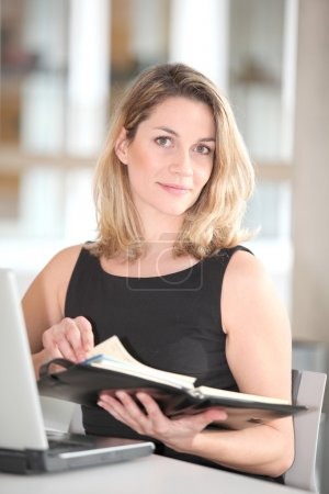 Businesswoman writing appointment on agenda