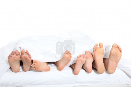 Closeup of family feet in bed