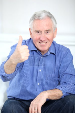 Photo for Portrait of smiling elderly man with thumb up - Royalty Free Image