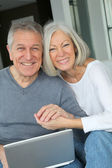 Senior couple assis dans le canapé avec ordinateur portable