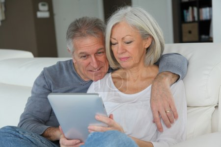 Photo for Senior couple sitting in sofa with electronic tablet - Royalty Free Image