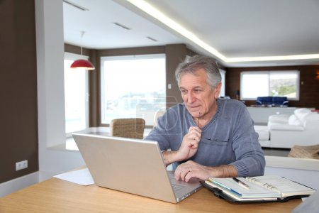 Senior man at home in front of laptop computer