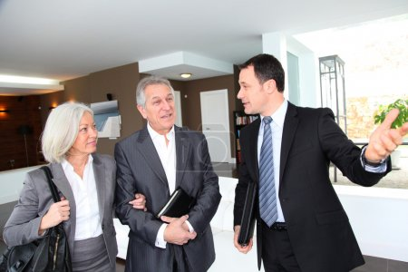 Seniorenpaar besucht modernes Haus mit Immobilienmakler