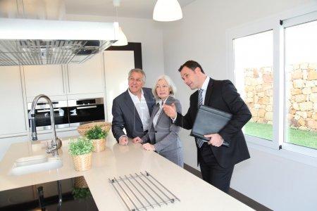 Photo pour Agent immobilier montrant l'intérieur de la maison au couple aîné - image libre de droit