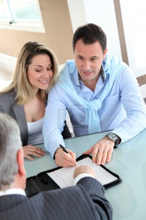 Happy couple signing purchase contract