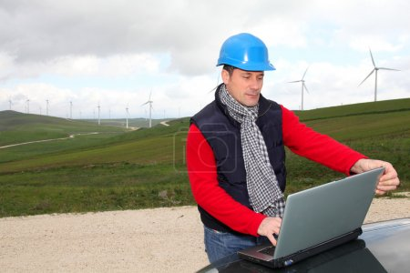 Photo for Engineer working on laptop computer in wind turbines field - Royalty Free Image