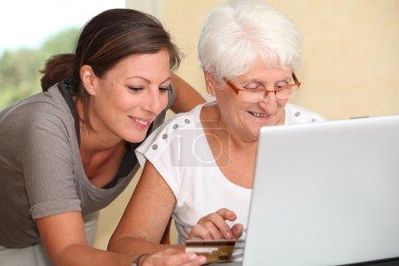 Photo pour Femme âgée et jeune femme faisant du shopping sur internet - image libre de droit