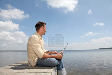 Man with laptop on a pontoon
