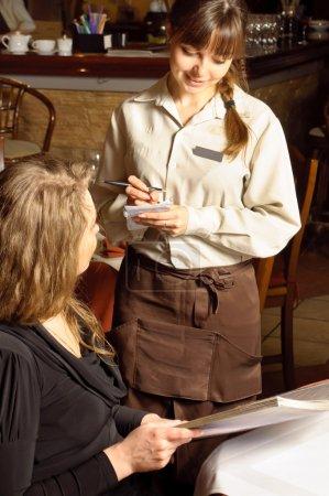 Photo pour Une belle femme dans le restaurant. maître d'hôtel prend l'ordonnance - image libre de droit