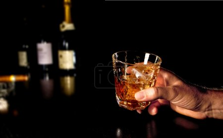 Holding a glass of Whiskey in Hand