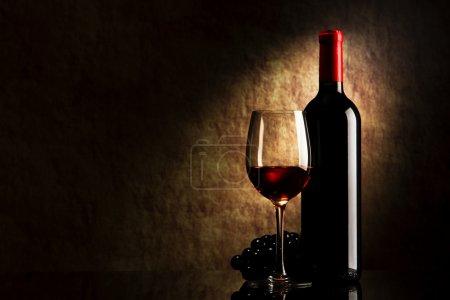 Photo pour Bouteille avec vin rouge et verre et raisins sur une vieille pierre - image libre de droit