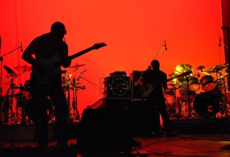 Photo pour Un groupe de rock tourné en silhouette alors qu'il jouait dans un théâtre - image libre de droit