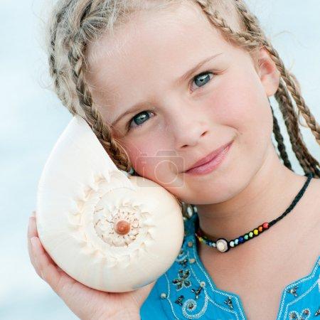 Photo pour Vacances d'été - belle fille avec coquille à la plage - image libre de droit