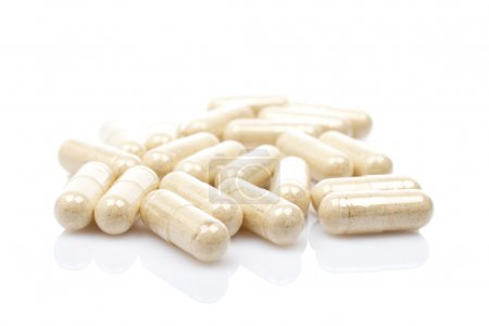 Photo for Capsules reflected on white background with shallow DOF - Royalty Free Image