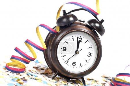 Photo pour En attendant le Nouvel An avec horloge, confettis et rubans. Profondeur de champ faible - image libre de droit