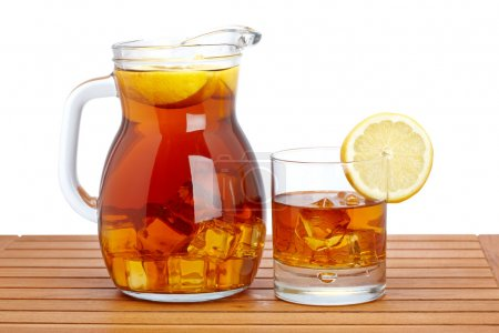 Photo for Ice tea pitcher and glasss with lemon and icecubes on wooden background. Shallow depth of field - Royalty Free Image