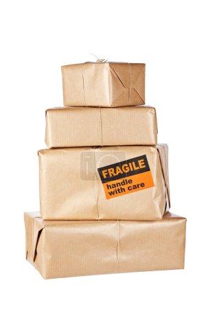Photo pour Empilement de paquets bruns isolés sur fond blanc. Profondeur de champ faible - image libre de droit