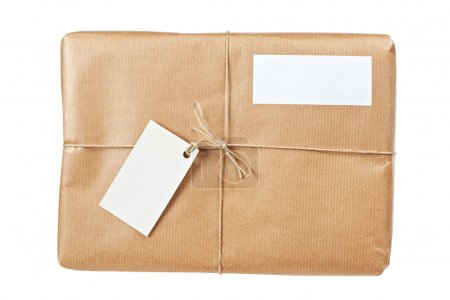Photo for A parcel wrapped in brown paper and tied with rough twine and two blank labels, isolated on white background. Shallow depth of field - Royalty Free Image