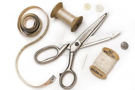 Photo for Tailor's tools - scissors, measuring tape, thimble, etc. - on white - Royalty Free Image