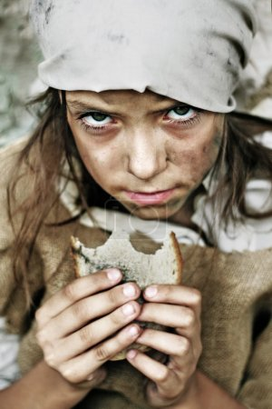 Photo for Child wearing vintage, dirty clothing, with a piece of bread in her hand - Royalty Free Image