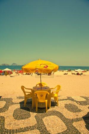 Photo pour Chaises de table jaunes et parasol sur la plage d'Ipanema - image libre de droit