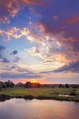 Beautiful sunrise and romantic clouds on the sky. Flood waters of Narew riv