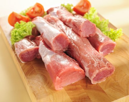 Photo for Pork tenderloin on a cutting board and vegetables - Royalty Free Image
