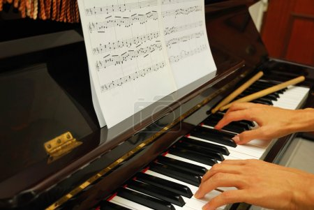 Both hands on piano keyboard with music score
