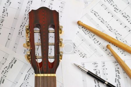 Guitar, drum sticks with pen on music score