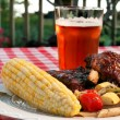 Perfect Holiday BBQ, complete with baby back ribs, corn on the cob, vegetables, and a wonderful wheat pale ale.