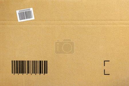Photo pour Fond en carton d'une boîte d'emballage fermée avec code à barres imprimé - image libre de droit