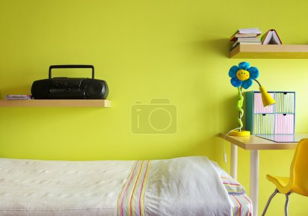 Photo for Detail of a teenager bedroom with desk, bed, shelf, and yellow wall - Royalty Free Image