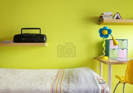 Foto de Detalle de un dormitorio adolescente con escritorio, cama, estante y la pared amarilla - Imagen libre de derechos