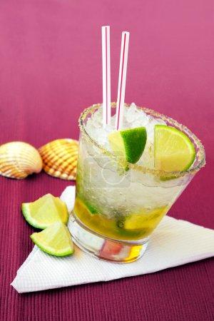 Photo pour Cocktail de caïpirinha brésilien avec des citrons verts et des coquillages sur un côté - image libre de droit