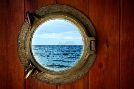 Photo pour Gros plan d'un hublot fermé avec vue sur l'océan - image libre de droit