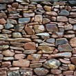 Background of a wet old rustic wall made of many p...