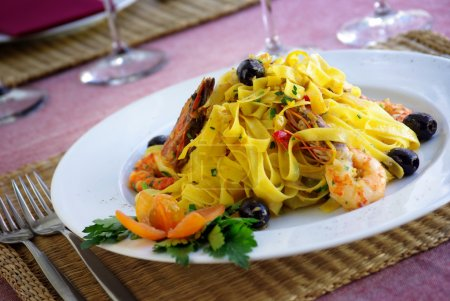 Photo for Italian dish of tagliatelle, shrimps and olives - Royalty Free Image