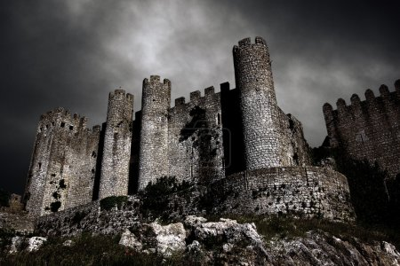 Photo for Disturbing scene with medieval castle at night with stormy sky - Royalty Free Image