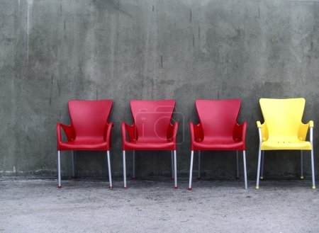 Photo for Row of four chairs. Three red, one yellow. - Royalty Free Image