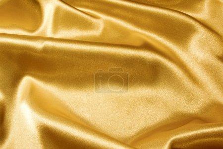 Photo pour Contexte d'un satin doré ondulé brillant - image libre de droit