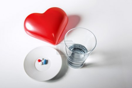 Photo for Concept image of glass of water and medical pills for heart diseases - Royalty Free Image