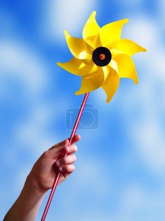 Photo pour Main d'enfant tenant un moulin à vent jouet jaune . - image libre de droit