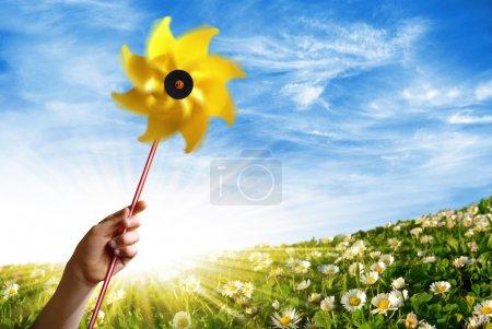 Photo pour Main d'enfant tenant un moulin à vent jaune dans un champ fleuri au printemps - image libre de droit